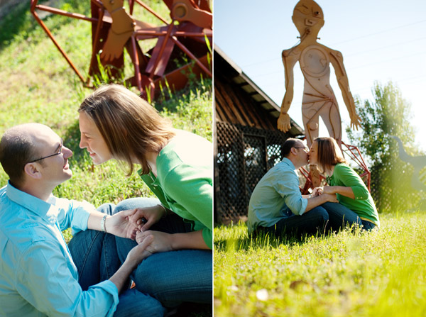 engagement portraits of engaged couple sitting in the grass under a giant sculpture kissing in downtown waxhaw nc